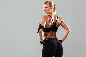 Back view portrait of a healthy muscular sportswoman standing