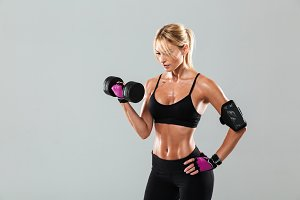 Young concentrated athlete woman doing exercises with a dumbbell