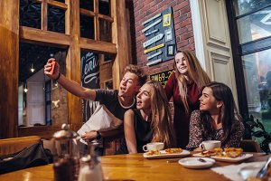 Excited friends taking selfie with smartphone sitting at table having night out.