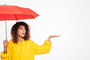 Picture of confused african woman in raincoat hiding under umbrella