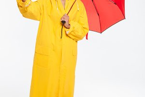 Full length image of happy african woman in raincoat