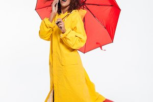 Full length image of surprised happy african woman in raincoat