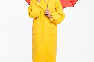 Full length image of surprised african woman in raincoat