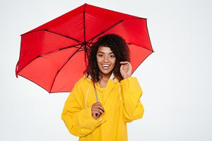 Smiling african woman in raincoat posing with umbrella