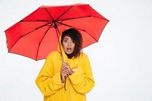 Surprised african woman in raincoat posing with umbrella
