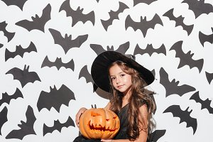 Pretty smiling little girl dressed in halloween costume