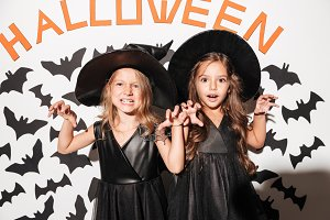 Couple of two little girls dressed in halloween costumes posing