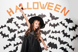 Happy little girl dressed in halloween costume holding lollipop