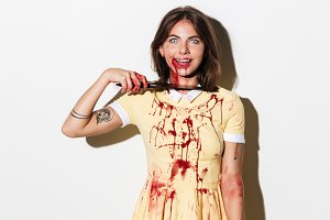 Mad smiling zombie woman cutting her throat with a knife