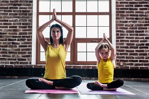 Female yoga instructor training little girl doing stretching exercise sitting in lotus position indoors