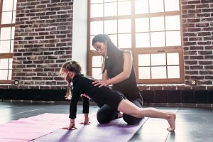 Young trainer helping little girl doing plank exercise in sports club