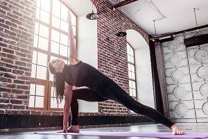 Young sporty woman practicing yoga doing triangle pose, trikonasana, on mat