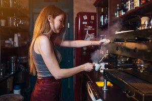 Stylish ginger girl making coffee using a professional coffee machine in coffee house