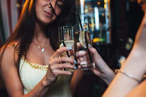Close-up shot of female friends toasting with glasses of cocktails during a party in bar