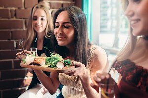 Group of girls having lunch in fashionable restaurant. Smiling young woman enjoying the smell of delicious salad served on wooden plate