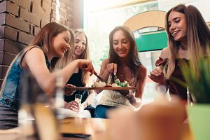 Group of laughing pretty young women sharing food sitting at coffee shop