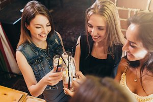 Top view of pretty smiling female friends clinking glasses of cocktails at bar