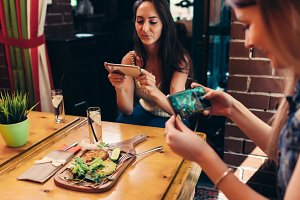 Young female food bloggers photographing their lunch with smartphones in restaurant