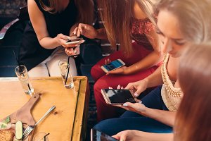 Group of pretty young female friends eating together in cafe using smartphones