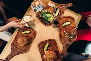 Food photography. Top view of hamburgers served with fresh vegetables, cucumbers on wooden boards in rustic style