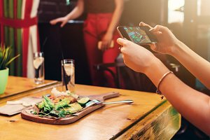 Close-up image of female hands holding a mobile phone taking picture of healthy delicious dish in cafe