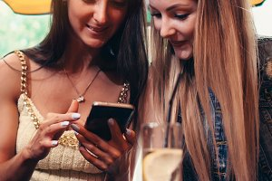 Two smiling Caucasian female friends watching photos and videos on smartphone sitting in coffee shop having lunch break