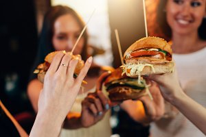 Female hands holding big tasty juicy hamburgers with blurred women in background