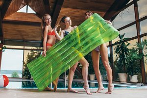 Attractive smiling slim female friends wearing swimsuits holding inflatable lounge posing in spa and wellness center