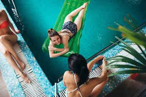 Top view of slim young female friends relaxing at hotel swimming pool