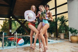 Three young female models posing in swimsuits holding pineapples, hat and juice at swimming pool at spa center