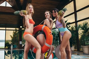 Group of pretty female friends wearing swimsuits having pool party at hotel