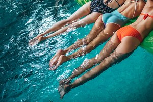 Close-up back view of female legs. Three fit women in swimwear swimming in blue sea water using air mattress