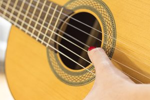 Hand playing acoustic guitar,