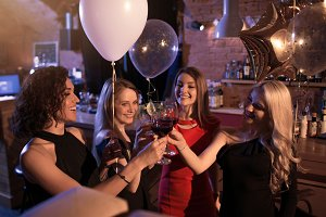 Group of cheerful girls having a party standing clinking glasses together at night club