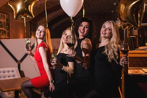 Smiling European girlfriends dressed in cocktail dresses drinking alcoholic beverages having bachelorette party in trendy restaurant