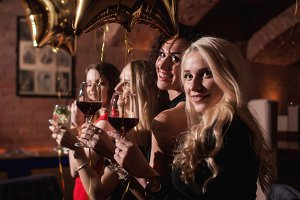 Cheerful young women standing looking back to camera holding glasses of wine celebrating birthday of their girlfriend in restaurant