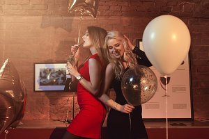 Portrait of two sexy girlfriends having fun drinking cocktail in modern restaurant decorated with balloons