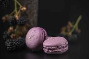 Sweet macaroons with blackberries on black bacground