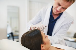 Young doctor doing botox injections on a female client's forehead