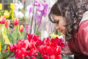 Beautiful woman smelling flowers