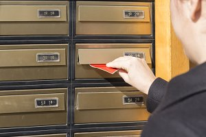 Woman inserting letter in a mailbox