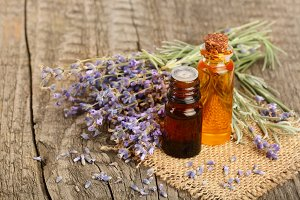 Herbal oil and lavender flowers on old wooden background
