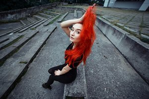 Style redhead girl sitting on outdoors. Woman with vibrant colorful hairstyle holding her hair and looking to camera. Wide angle portrait