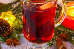 New Year's mulled wine in a glass on the background of twigs, candles and garlands.