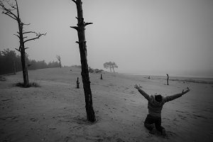 Monochrome of Depressed Man n Has on a Lap Raised Hands Up Against the Background of Dead Trees.