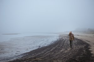 Lonely sad man walking on a foggy beach