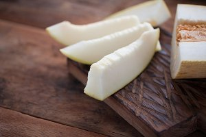 Fresh pieces of melon on the wooden background