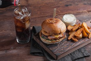 A tasty Burger with snacks in the form of potatoes with white garlic sauce and a glass of cold Cola. juicy Burger with onion rings, bacon and cheese on a dark wood background