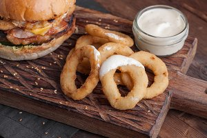 Close up of fried onion rings on the Board, with a white garlic sauce on wooden background