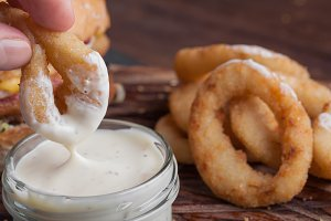 Closeup of male hand dipping in white garlic sauce fried onion rings